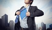 Image of young businessman showing superhero suit underneath his shirt standing against city backgro