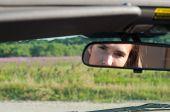 Brunette woman watching on rear-view mirror