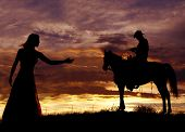 stock photo of western saddle  - A cowboy is sitting on a horse in the sunset swinging a rope - JPG