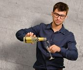 Young Man Pouring Champagne Into Glass Against Wall