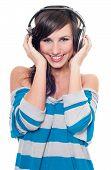 Smiling female listening music through headphones isolated on white