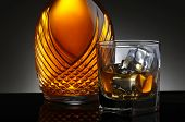 Closeup of an elegant decanter and a glass of scotch on the rocks. Horizontal format on a light to d