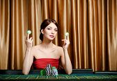 Woman with chips sitting at the casino table at the gambling house