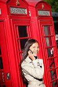 Woman taking on smartphone by London red phone booth. Young casual female business woman having conv