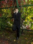 Boy In Black Suit Said By Telephone Amid Foliage