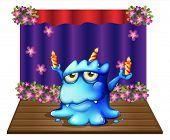 Illustration of a stage with a blue monster balancing the three lighted candles on a white background