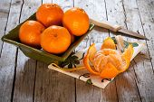 stock photo of clementine-orange  - Bowl with honey tangerines and peeled tangerine on antique wood table - JPG
