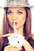 Young brunette with hat, holding four aces and showing shush sign with index finger on her lips - st