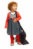 picture of big-foot  - Toddler girl in big shoes carrying big moms bag and looking away isolated on white background - JPG