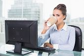 Calm brunette businesswoman drinking from disposable cup in bright office