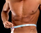 image of flat stomach  - man with a muscular body measuring his abs  - JPG