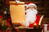 Santa Claus in wooden home interior holding blank wish list scroll