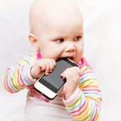 Little Baby Baby Chews On A Mobile Phone In Colorful Striped Clothing