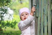 Brown Eyed Baby Girl In Pink Plays With Old Green Wooden Wicket