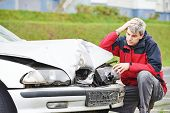 stock photo of driver  - Adult upset driver man inspecting automobile body after crash car collision accident - JPG