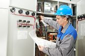 One electrician builder at work checking wire with drawing inspecting high voltage power electric li
