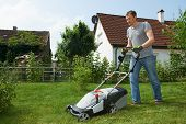 man cutting grass in his garden yard with lawn mower