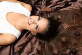 stock photo of atlas  - Woman lying on brown atlas covered by chocolate and candies - JPG