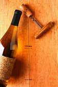A chardonnay wine bottle and corkscrew on a rustic wood surface. Viewed from above the bottle is par