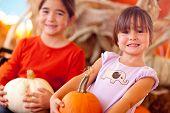Cute Little Girls Holding Their Pumpkins At A Pumpkin Patch One Fall Day.