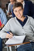 Portrait of handsome young man with exam paper sitting at desk in classroom