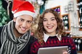 Portrait of happy young couple with digital tablet at Christmas tore