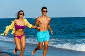 Teen Couple Running Together On Beach.