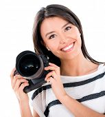 Happy female photographer holding a camera - isolated over white background