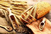 Rye spikelets and bread on wooden background