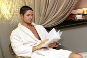 Handsome man in white robe is reading a book while sitting on a chair at a hotel