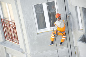 image of mortar-joint  - Facade plasterer at outdoor wall renovation making off joints - JPG