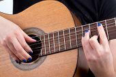 woman fingers playing guitar