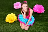 Beautiful young woman in petty skirt with flowers on grass