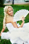 Happy Bride With Fan On Grass