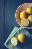 Sliced and whole lemons on wooden table
