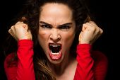 stock photo of clenched fist  - A very angry aggressive woman is clenching her fists in rage - JPG