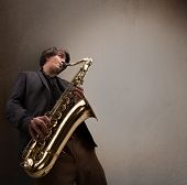 stock photo of saxophone player  - Handsome young musician playing on saxophone - JPG
