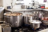 picture of stew pot  - Cooking in a commercial kitchen with large stainless steel pots filled with stew and vegetables on a central gas hob - JPG