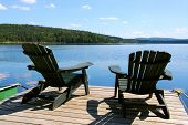 Two adirondack wooden chairs on dock facing a blue lake with clouds reflections