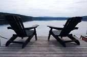 Two wooden adirondack chairs on a boat dock on a beautiful lake in the evening