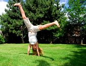 Young girl doing a cartwheel on green grass