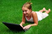Young girl lying on grass in a park with laptop computer