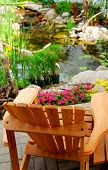 Natural stone pond and wooden patio chair as landscaping design element