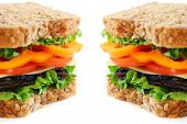 Big healthy sandwich with vegetables and meat close up on white background