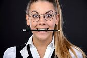 stock photo of insane  - Young nerd woman crazy expression in glasses holding a pencil in her mouth on black background - JPG