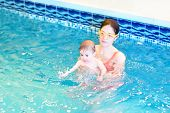 Young Mother And Baby Playing In A Swimming Pool