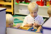 Young Preschool Children Playing Building Blocks In School Classroom