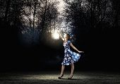 Young woman in blue dress walking in night wood