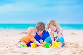 foto of sunny beach  - Three kids teen age boy little toddler girl and a funny baby playing together digging in sand with colorful toys spade and buckets relaxing on a sunny tropical beach during family summer vacation - JPG