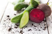 Fresh cucumbers and beet on wooden table, close-up.